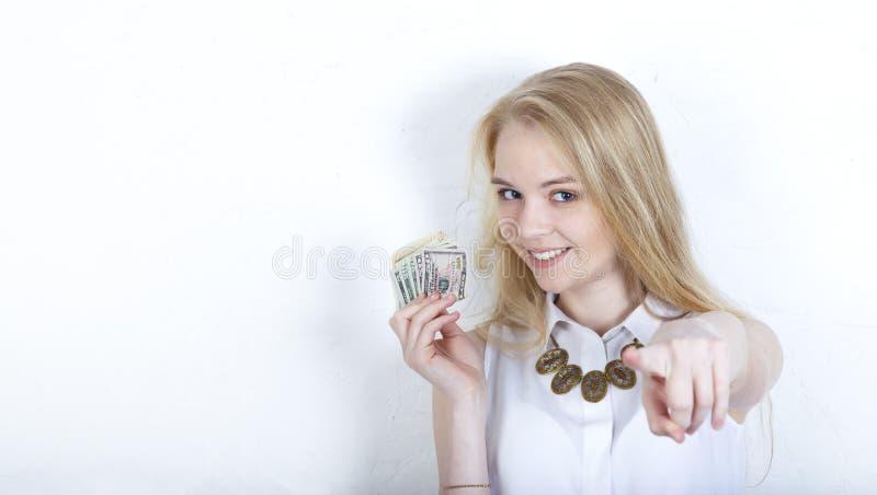 молодая белокурая девушка держа доллары, указывая ее жест пальца на камеру и на вас, знака руки, положительных и уверенных внутри стоковое фото