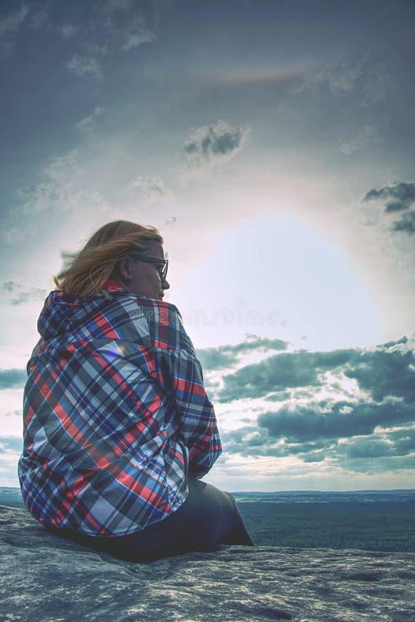 Молодая белокурая девушка сидит на пике и наслаждается солнцем Hiker женщины стоковое изображение