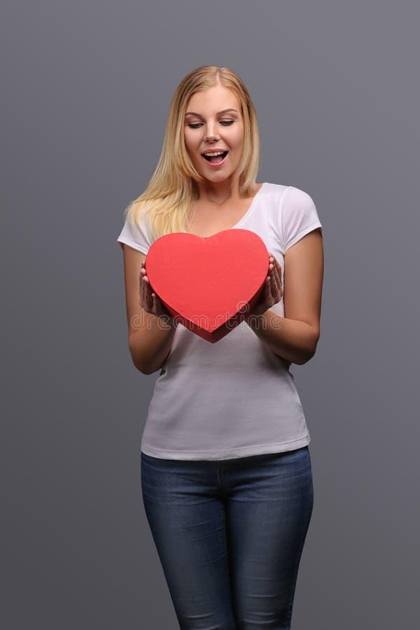 Молодая белокурая девушка с подарком в руке, красной в форме сердца Эмоции утехи и сюрприза на стороне Изолят на сером цвете стоковые изображения rf