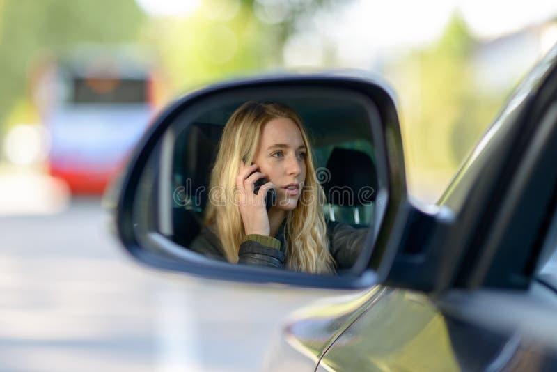 Молодая белокурая женщина в зеркале крыла автомобиля стоковая фотография