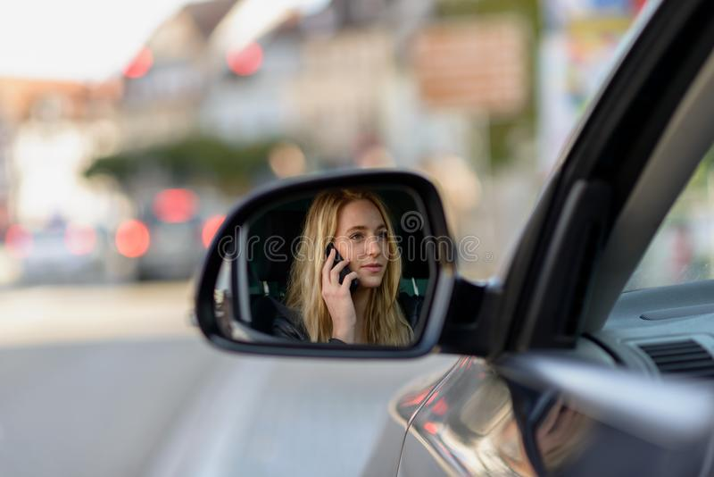 Молодая белокурая женщина в зеркале крыла автомобиля стоковые фото