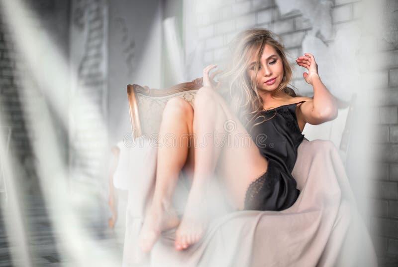 Молодая белокурая женщина в сексуальном черном женское бельё сидит в кресле с одной рукой под головой стоковая фотография