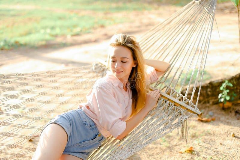 Молодая белокурая женщина лежа в белом плетеном гамаке на песке, нося джинсы замыкает накоротко стоковые изображения