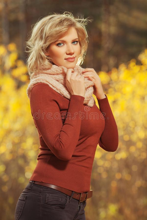 Молодая белокурая женщина моды в коричневом пуловере и шарфе пинка на открытом воздухе стоковые фотографии rf