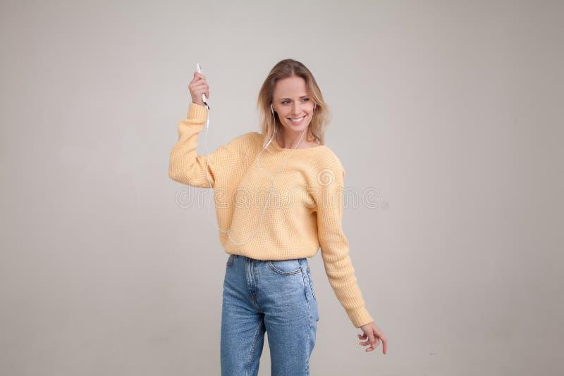 Молодая белокурая женщина нося желтый свитер вспоминая славные памяти как танцы с наушниками lisening музыка, держа смартфон и стоковые изображения