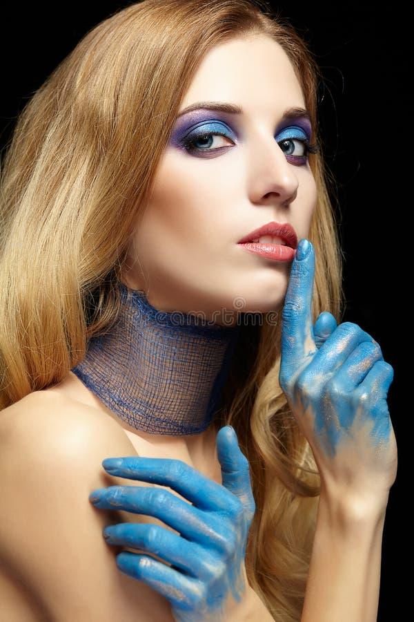 Молодая белокурая женщина при длинные волосы и руки покрашенные в голубом pai стоковая фотография