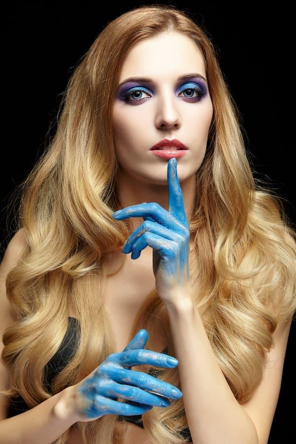 Молодая белокурая женщина при длинные волосы и руки покрашенные в голубом pai стоковое фото rf