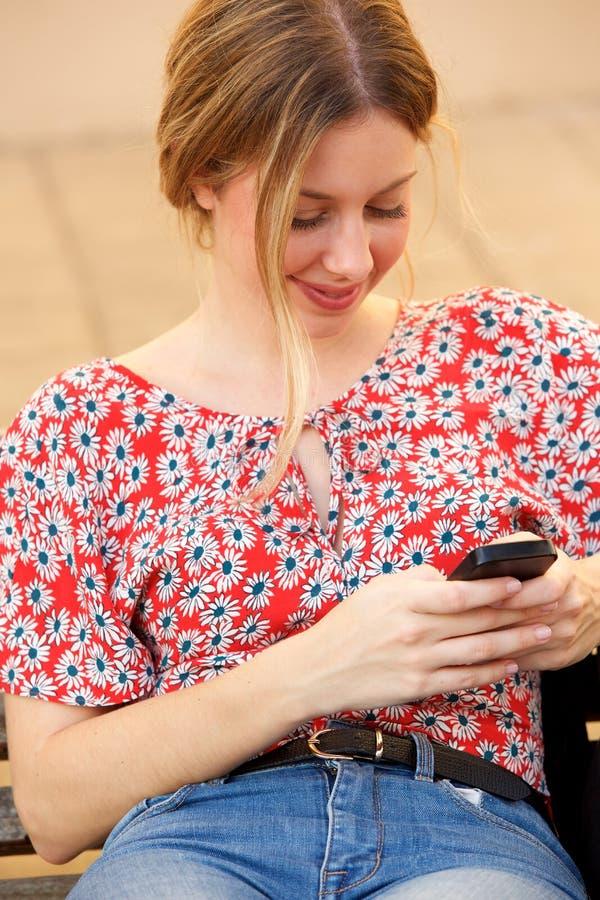 Молодая белокурая женщина смотря сотовый телефон стоковое фото rf
