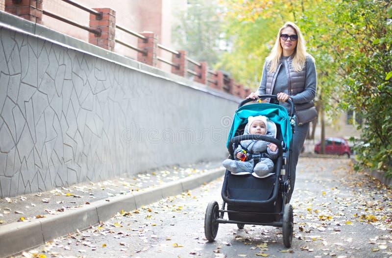 Молодая белокурая женщина с прогулочной коляской идя для прогулки в парке стоковое фото