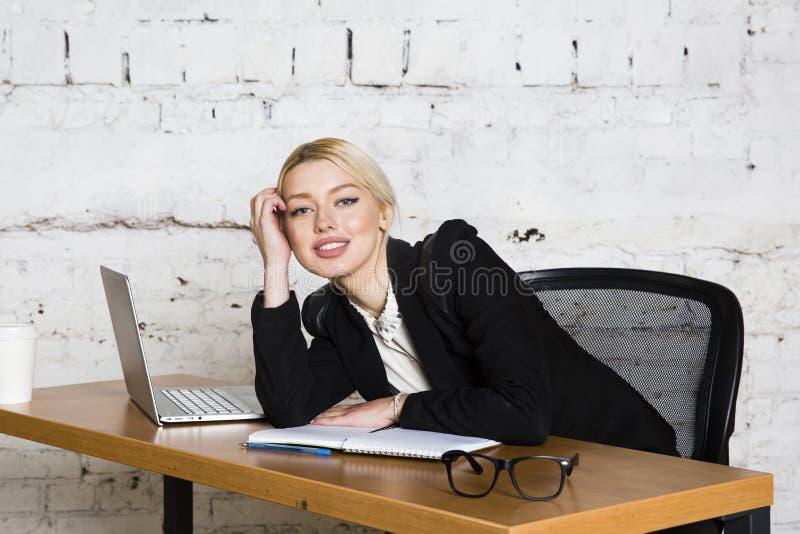 Молодая белокурая коммерсантка красоты сидя на таблице офиса с компьтер-книжкой, тетрадью и стеклами в костюме владение домашнего стоковое фото rf
