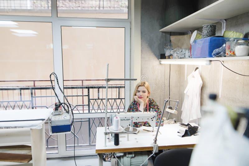 молодая белошвейка сидит на рабочем месте в современной студии Современная студия дизайна дизайнерской одежды стоковое фото rf