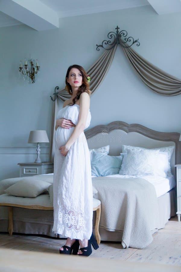 Молодая беременная женщина в белом платье стоковое фото
