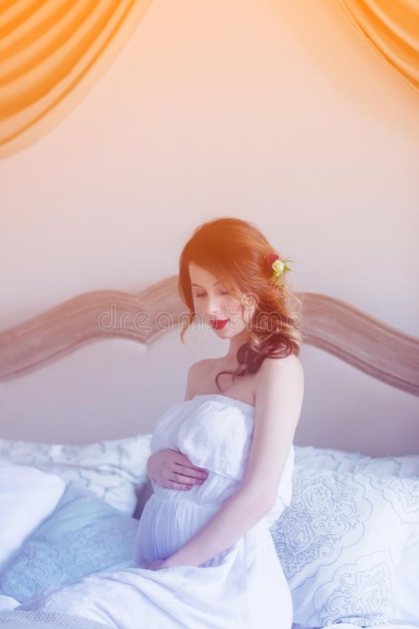 Молодая беременная женщина в белом усаживании платья стоковая фотография rf