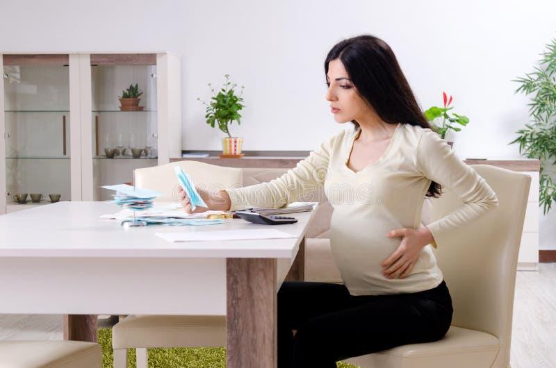 Молодая беременная женщина в концепции бюджетного планирования стоковые изображения rf