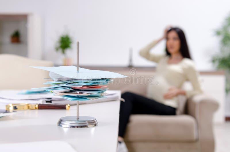 Молодая беременная женщина в концепции планирования бюджета стоковое фото rf