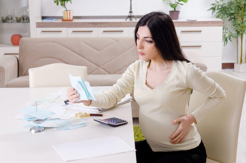 Молодая беременная женщина в концепции планирования бюджета стоковая фотография rf