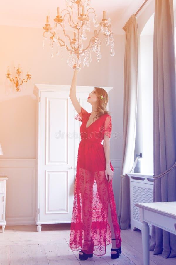 Молодая беременная женщина в красном положении платья стоковые изображения