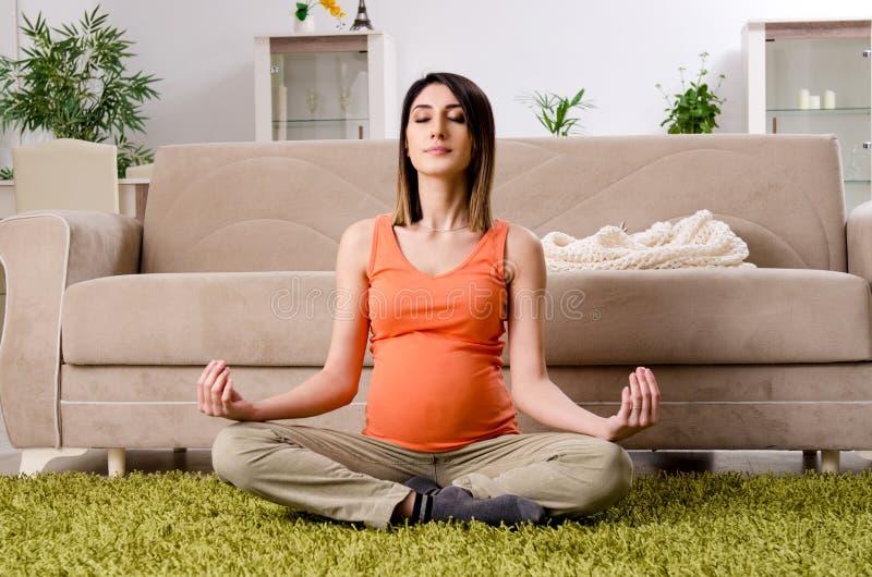 Молодая беременная женщина дома стоковые фотографии rf