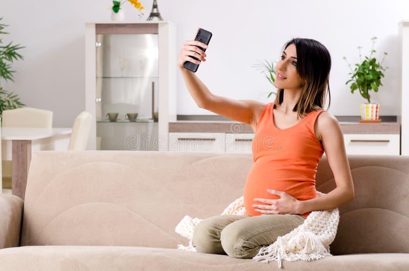 Молодая беременная женщина дома стоковые фото