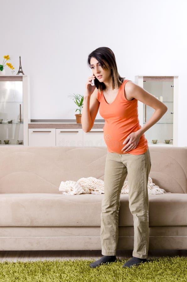 Молодая беременная женщина дома стоковое фото