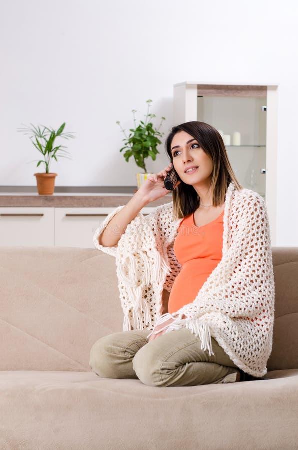 Молодая беременная женщина дома стоковая фотография