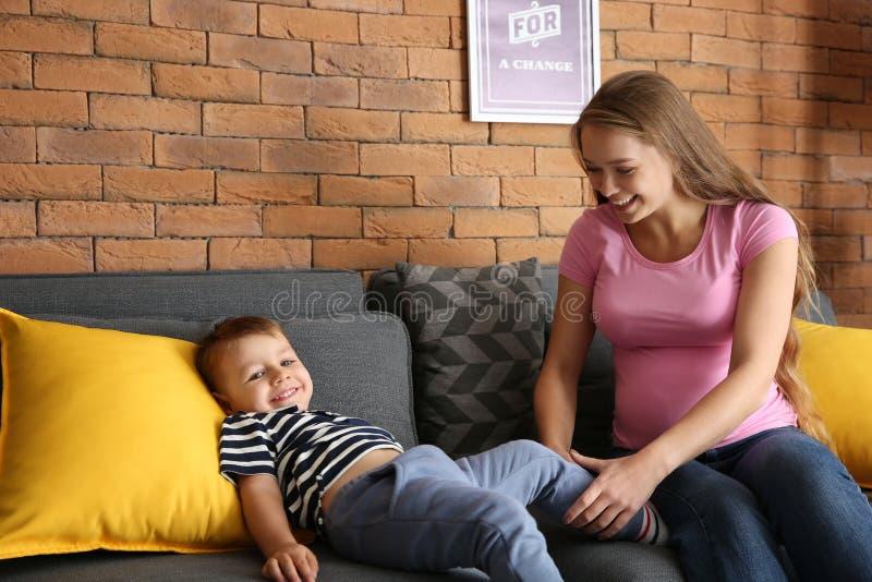 Молодая беременная женщина играя с ее милым маленьким сыном дома стоковая фотография rf