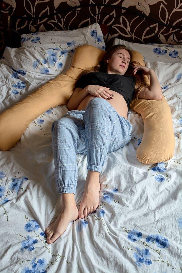 Молодая беременная женщина Беременная красивая женщина спит на подушке материнства в кровати стоковая фотография