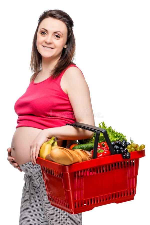 Молодая беременная женщина с корзиной фруктов и овощей на whi стоковое фото rf