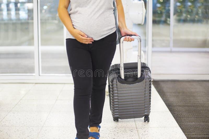 Молодая беременная женщина с чемоданом на авиапорте стоковая фотография rf