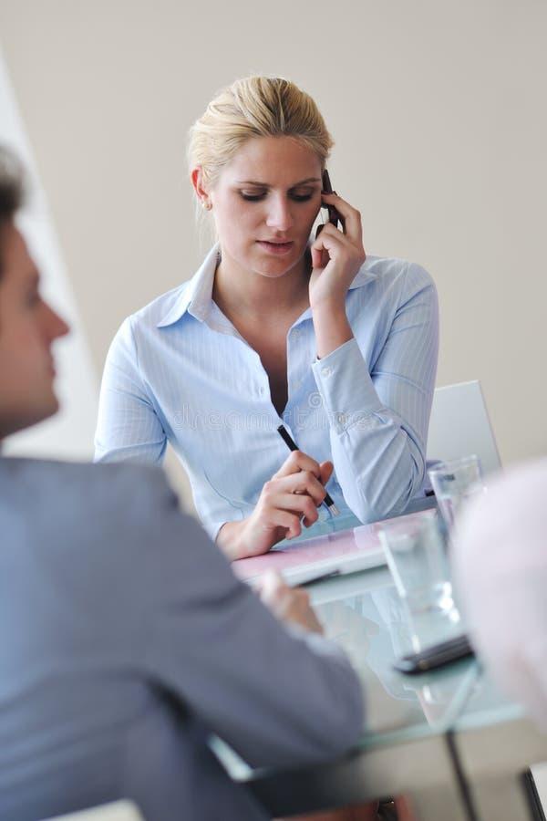 Молодая беседа женщины дела мобильным телефоном на meetng стоковое изображение