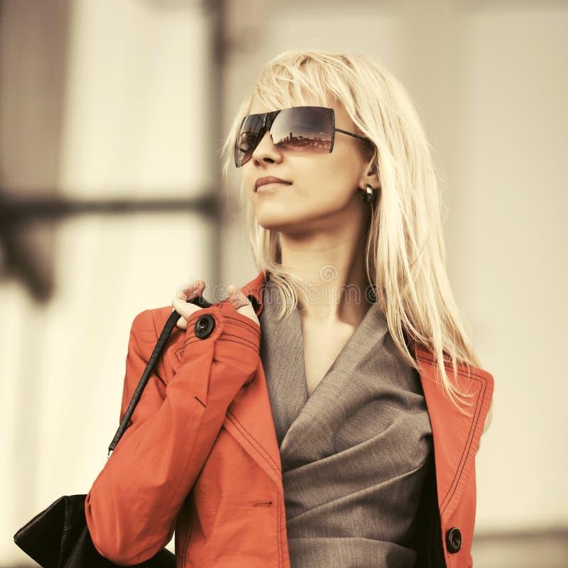Молодая бизнесменка моды в солнцезащитных очках ходит по улицам города стоковое фото rf