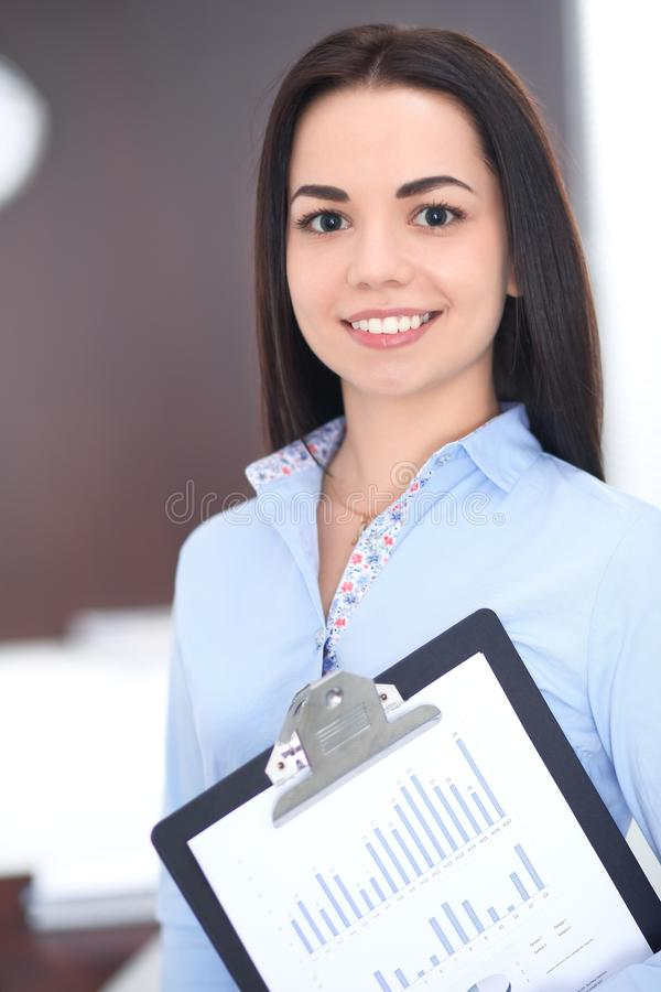 Молодая бизнес-леди брюнет выглядеть как девушка студента работая в офисе Испанская или латино-американская девушка счастливая на стоковые изображения rf