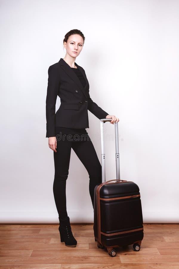 молодая бизнес-леди в черном костюме с чемоданом багажа стоковое изображение rf