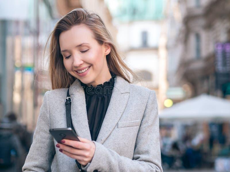 Молодая бизнес-леди используя ее телефон на улице стоковое фото rf