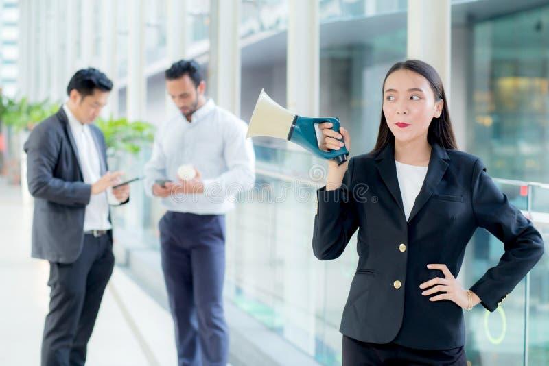 Молодая бизнес-леди работая на офисе держа мегафон стоковое фото rf