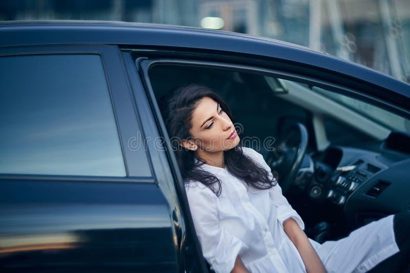 Молодая бизнес-леди сидя в автомобиле на сидении пассажира стоковое фото