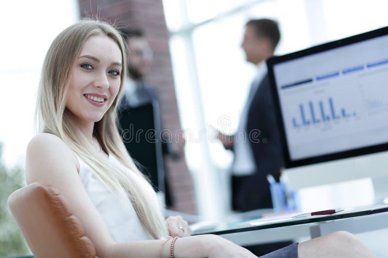 Молодая бизнес-леди сидя на столе в офисе стоковое фото rf