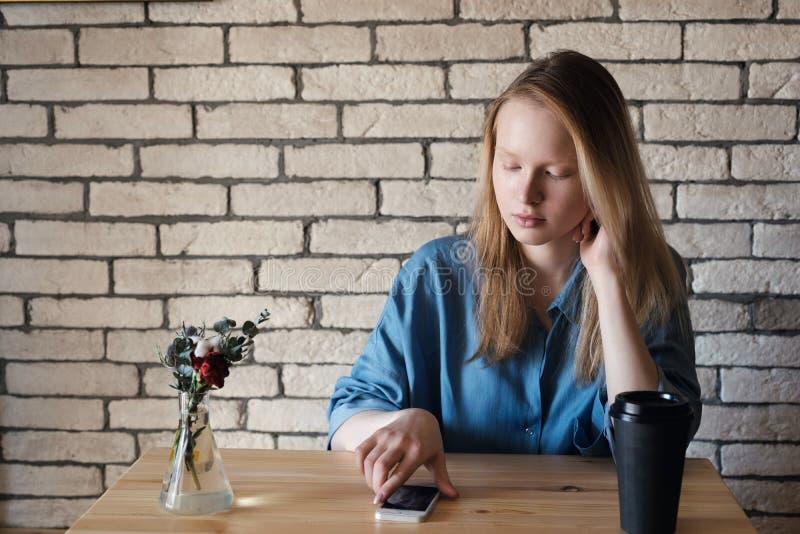 Молодая блондинка в голубой рубашке сидит на таблице в кафе на котором стоковое изображение rf