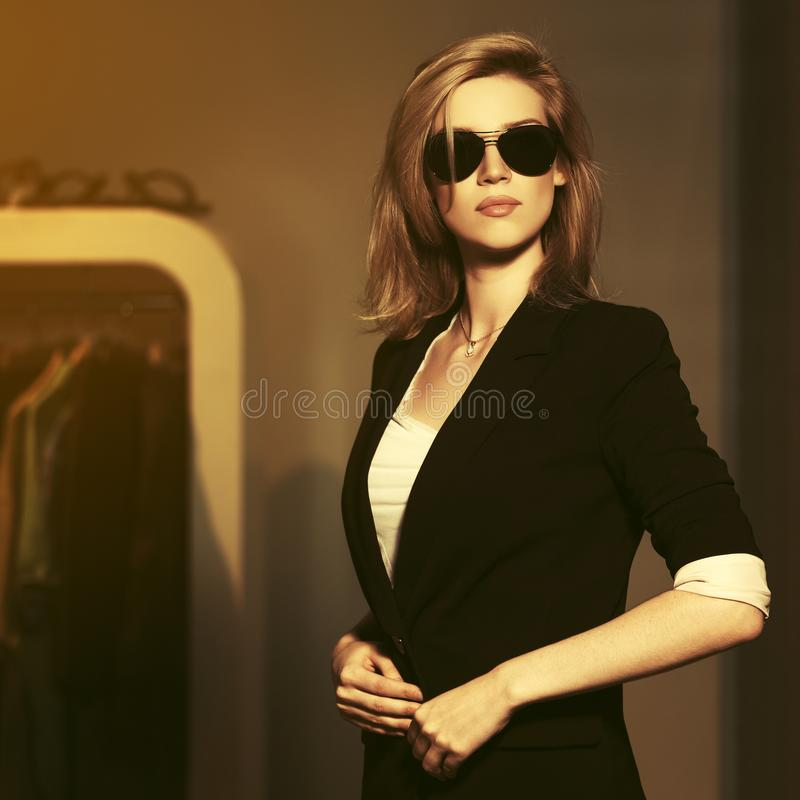 Молодая блондинка в солнцезащитных очках и в черном пиджаке стоковая фотография