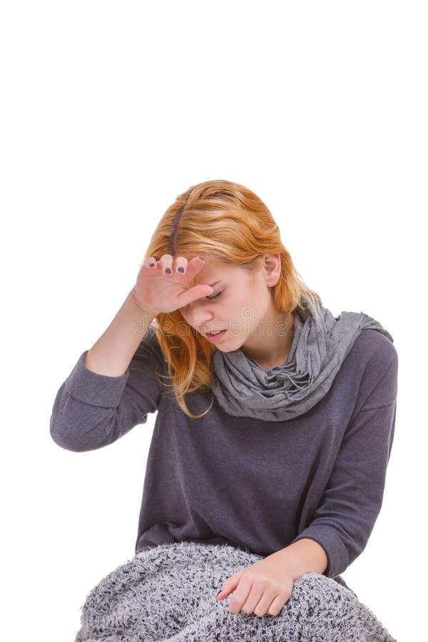 Молодая больная девушка держа дальше к головным демонстрируя головной боли или лихорадке белизна изолированная предпосылкой стоковая фотография rf