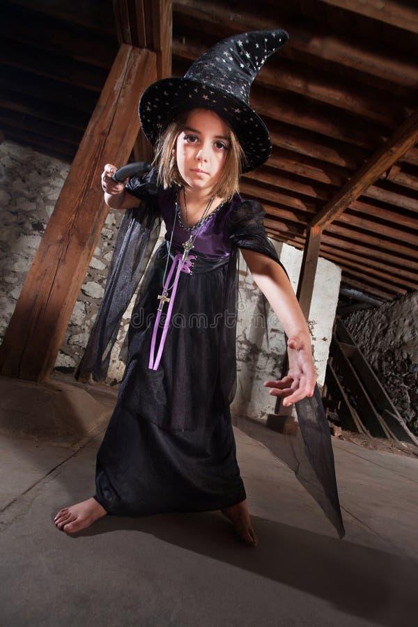Молодая ведьма указывая ее штат стоковые фото