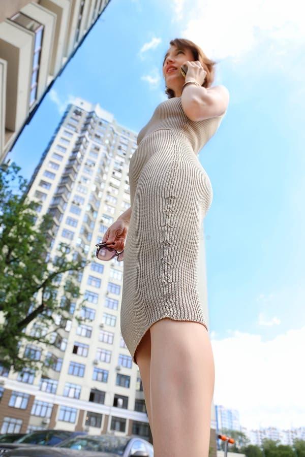Молодая взрослая женщина в связанной шелком юбке карандаша говоря со смартфоном на улице города outdoors Современная коммерсантка стоковые фотографии rf
