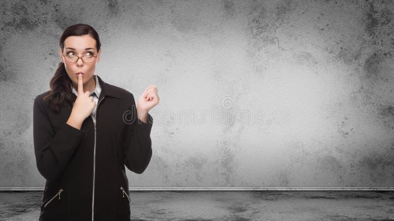 Молодая взрослая женщина смотря к бортовому положению перед стеной пробела пробела Grungy с космосом экземпляра стоковое фото rf