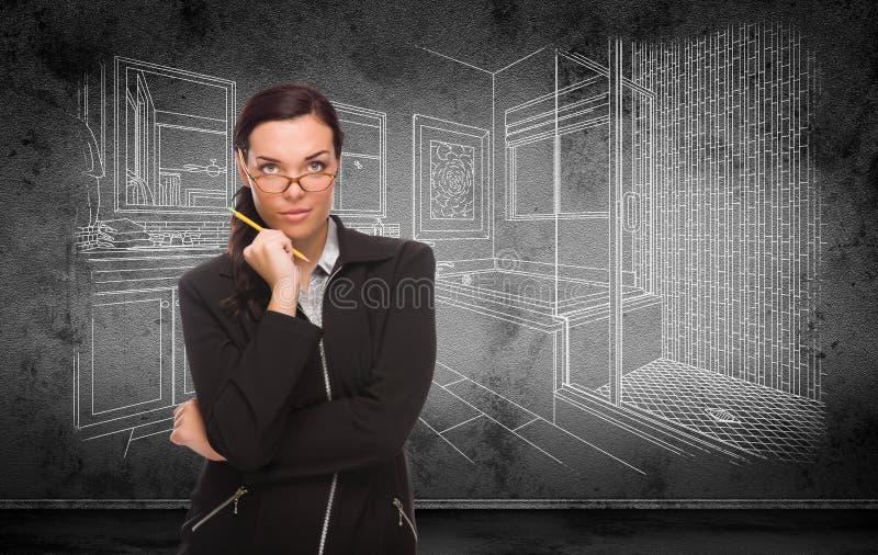 Молодая взрослая женщина с карандашем перед чертежом дизайна Bathroom на стене стоковые фото