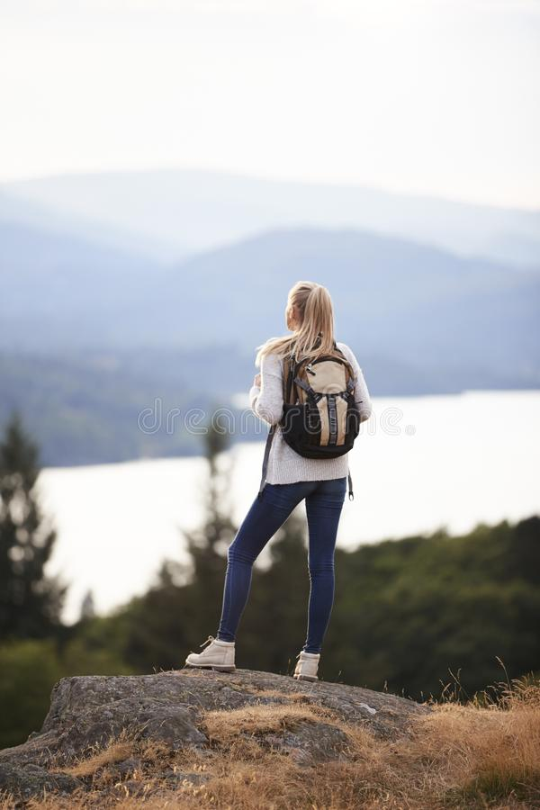 Молодая взрослая кавказская женщина стоя самостоятельно на утесе после пешего туризма, восхищая вид на озеро, задний взгляд стоковое изображение