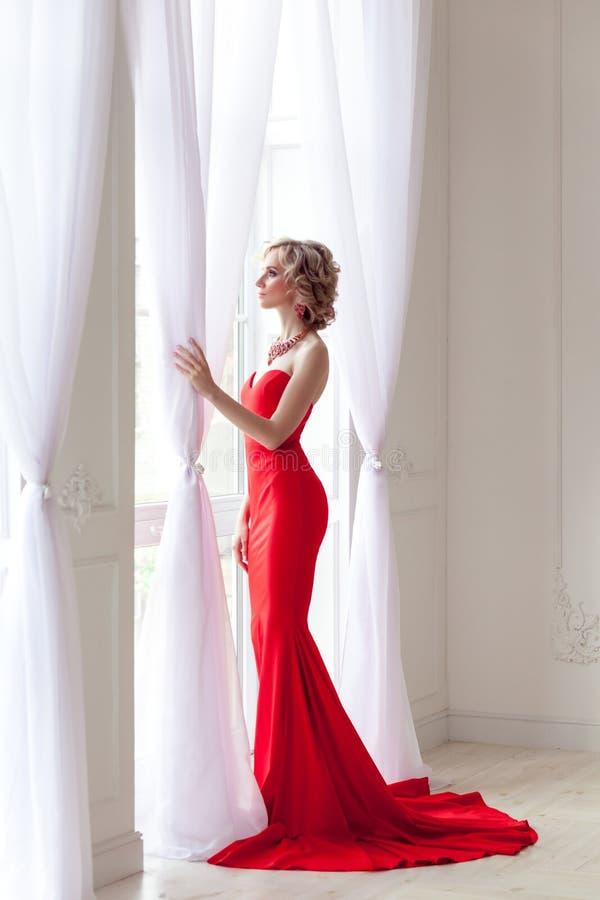 Молодая взрослая элегантная женщина с совершенным составом и красным длинным платьем стоковое фото rf