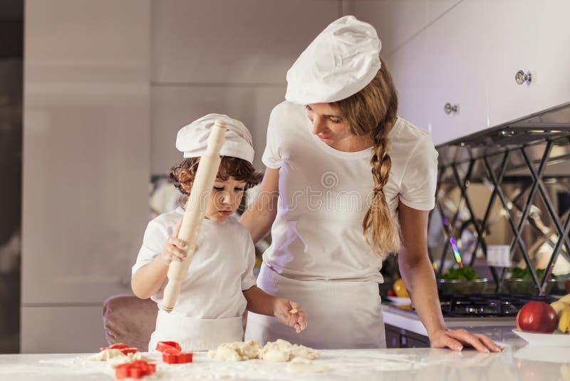 Молодая выпечка матери вместе с ее маленьким сыном в современной белой кухне стоковое фото