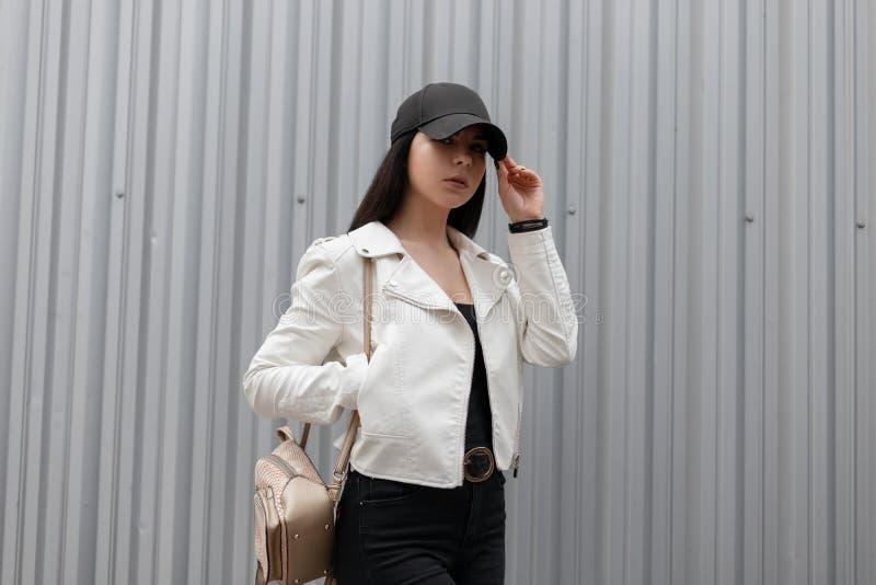 Молодая городская женщина брюнета в модной белой кожаной куртке в винтажных джинсах в футболке в стильной черной крышке стоковые фото