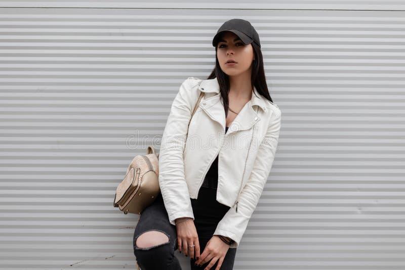 Молодая городская женщина в ультрамодной белой кожаной куртке в винтажных сорванных джинсах в стильной черной бейсбольной кепке стоковое изображение