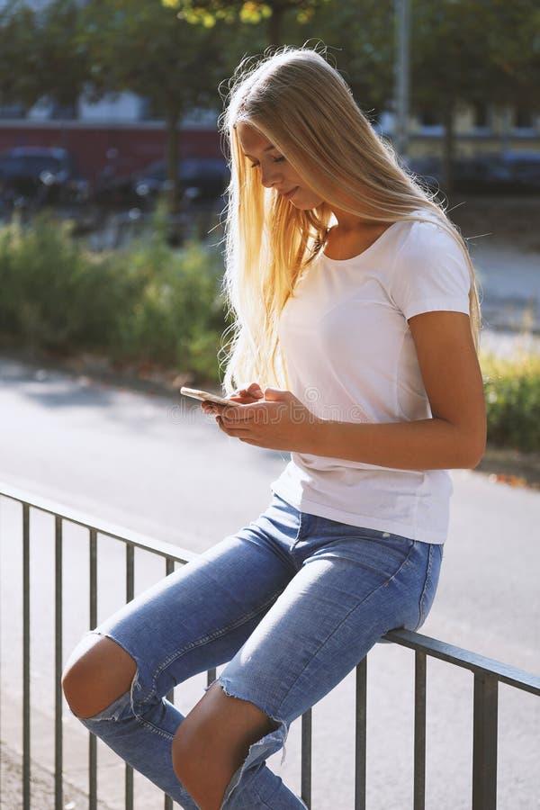 Молодая городская женщина используя чернь смартфона на улице стоковые изображения rf